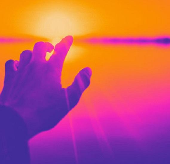 Purple hand transmitting energetic light language frequencies